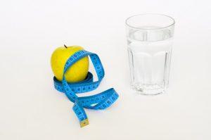 pohar vody, jablko a centimeter